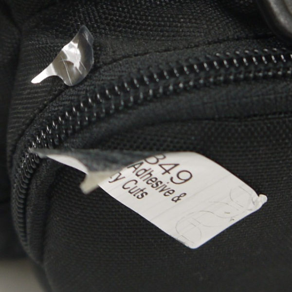 Silver tamper evident security label with security cuts attached to fabric